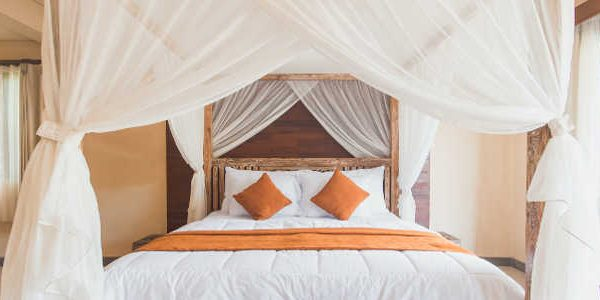 A canopy bed with white linene and burnt orange trim and pillows situated in a room.