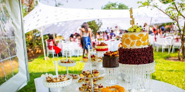 Cakes and other party foods stacked on a table wiith people enjoying themselves in the background.