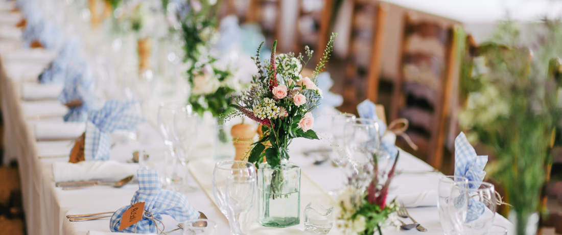 A beautifully decorated wedding table with white minen, flowers and cutlery