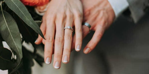 Image of bride and grooms hands, with wedding rigns.